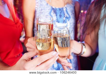 Group of girls cheering with fizzy champagne