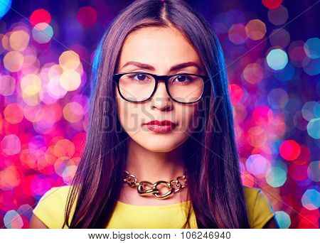 Young Asian woman in eyeglasses looking at camera on sparkling background