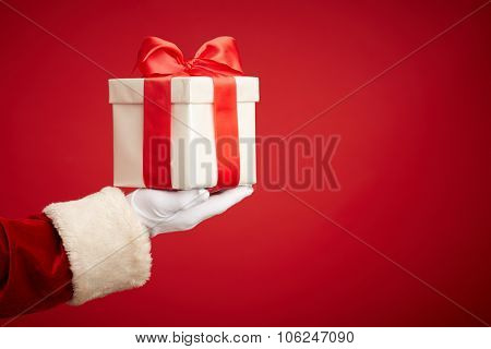 Santa hand holding giftbox with surprise