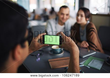 Friend taking photo of young couple on the phone