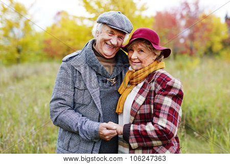 Positive loving senior couple posing for camera