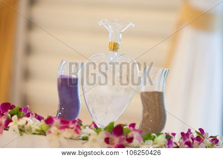 Glasses Of Colored Sand Sitting On A Table Covered With A White Tablecloth To Be Used For A Wedding