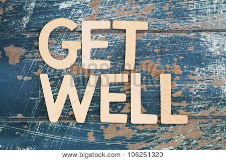 Get well written with wooden letters on rustic wooden surface
