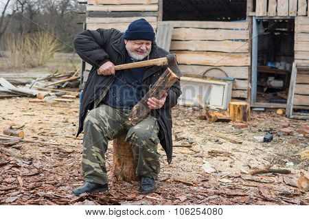 farmer is trying to pull out an axe from log