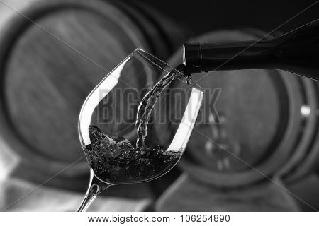 Pouring red wine from bottle into glass,  black and white retro stylization