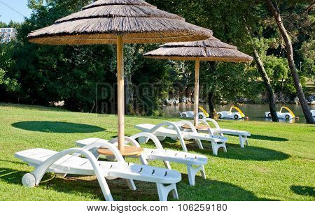 Umbrellas And Lounges On The Coastline In Porec, Croatia