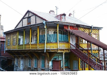 Old House With Carved Wooden Yellow Balcony And Staircase In Tbilisi, Old Town