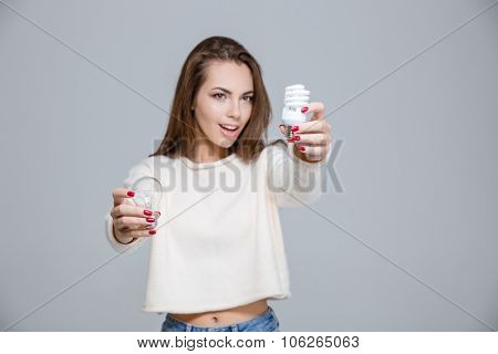 Portrait of a happy woman holding saving light bulb and normal light bulb over gray background