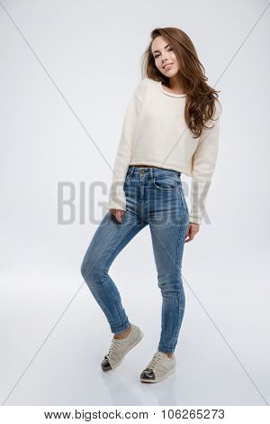 Full length portrait of a happy casual woman posing isolated on a white background