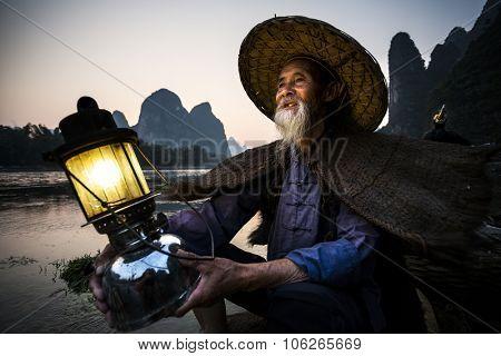 portrait by gas lamp of a traditional cormorant fisherman on Li river near Xingping, Guangxi province, China.