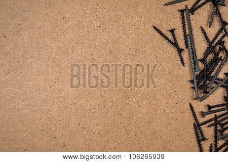 Iron screws on brown fibreboard