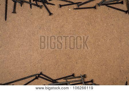 Iron screws on light brown fibreboard