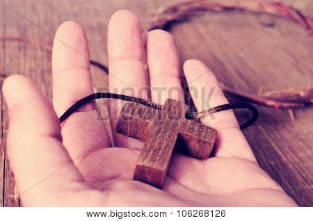 a wooden cross in the hand of a young man and a depiction of the crown of thorns of the Christ on a rustic wooden surface, with a filter effect