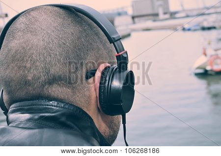 closeup of a young caucasian man seen from behind listening to music with headphones in front of the sea, with a filter effect