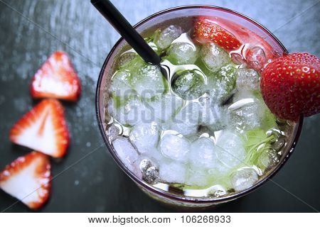high-angle shot of a glass with a strawberry mojito garnished with a strawberry on a black slate background