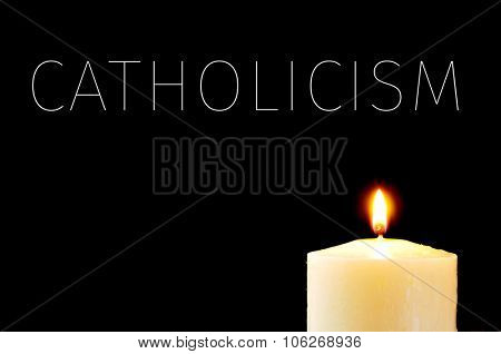a lit candle and the word Catholicism written in white on a black background