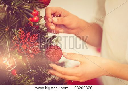 Woman hanging christmas decorations on tree at home in the living room