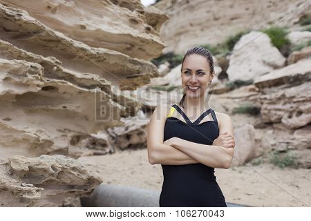 Young happy female runner posing while relaxing after morning jog