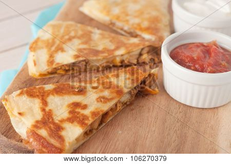 homemade chicken mexican quesadilla on wooden chopping board with a side of salsa
