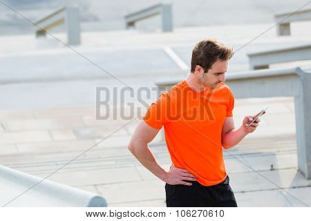 Fit men reading message on cell telephone while taking break between workout outdoors
