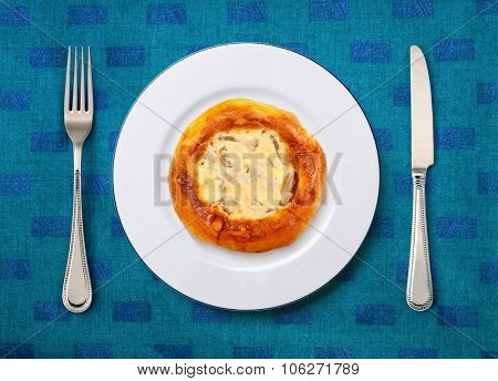 round white plate with pizza, knife and fork on table