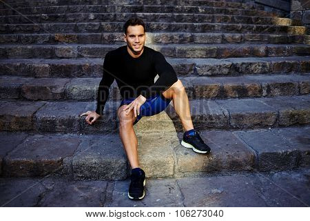 Smiling young male jogger relaxing after intense exercising in the fresh air