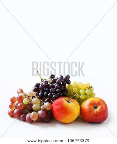 Fruity harvest background. Apples and grapes on a white.
