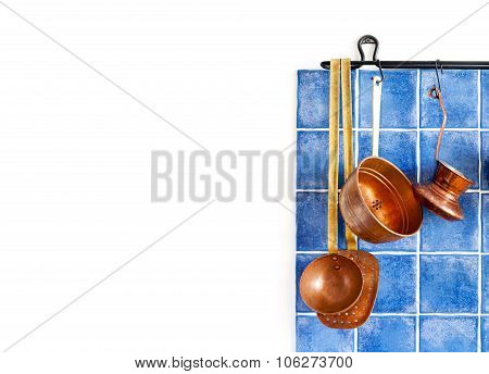 Retro brass utensils. cookware, chief kitchenware set on the blue tiles wall.