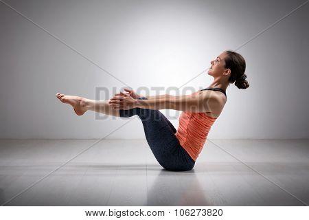 Beautiful sporty fit yogini woman practices yoga asana Paripurna navasana - boat pose beginner variation