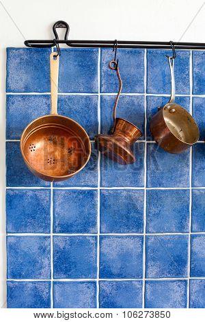 Copper kitchenware set. Pot, coffee maker, colander hanging on.