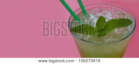 Tarragon, mint lemonade in the glass. pink background