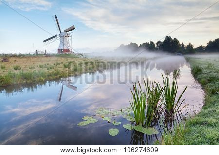 White Dutch Windmill In Misty Morning