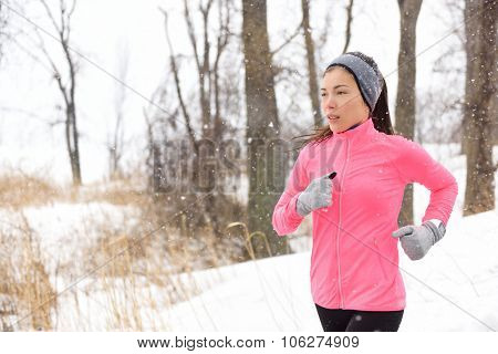 Winter jogging - young Asian Chinese adult woman runner running breathing cold air wearing pink windbreaker jacket, headband and gloves doing a cardio workout.