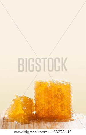 Organic honeycomb on the wooden board and pastel background. Tasty yellow, gold honey combs texture