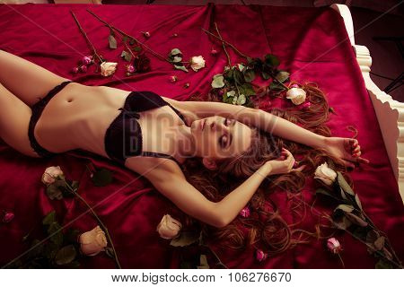 Sexy Slim Girl In Lingerie Lying On The Red Bed With Flowers