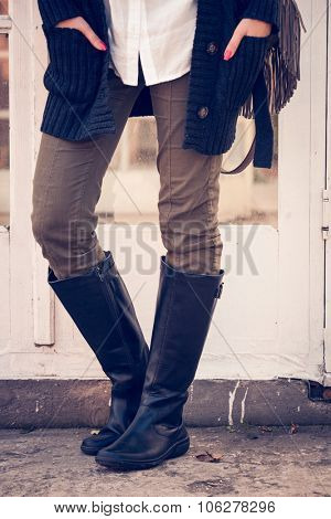 female legs in black leather high boots, pants, sweater and shirt, stand in front glass door, closeup, outdoor shot