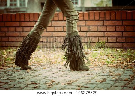 woman walk in dark green tassel boots in front small brick wall on cobble path, day shot