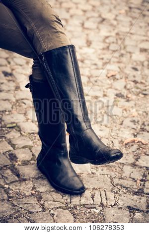 woman legs in black  autumn high heels boots on cobble, selective focus