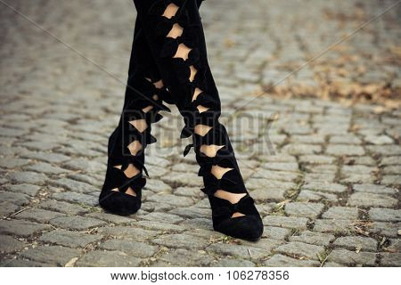 female legs in black  autumn high heels boots on cobble, closeup, selective focus