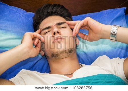 Young with Headache Lying in Bed