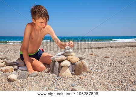 Boy building pebble castle on a beach