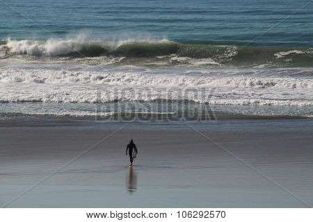 Solitary surfer on beach, ocean waves