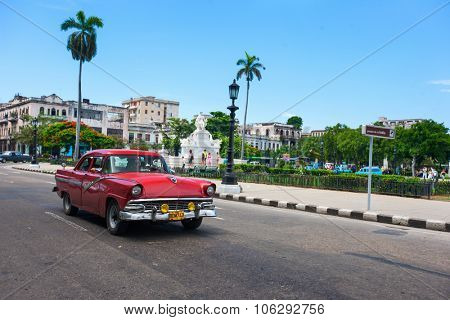HAVANA, CUBA - JULY 16, 2013: Authentic view of a street of Old Havana with old vintage American car and people on background.