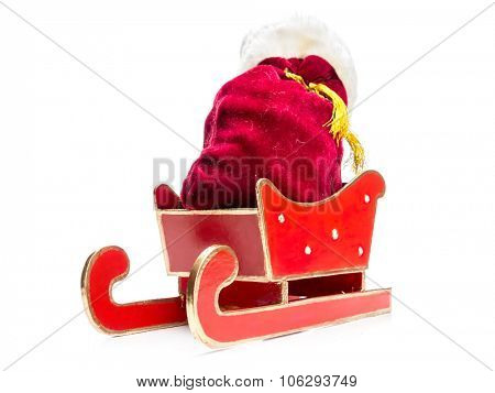 Santa Claus bag full of christmas presents in red sleigh over white background