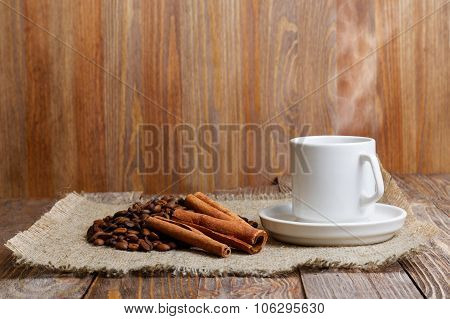 Steaming Cup Of Hot Coffee, Coffee Beans And Cinnamon