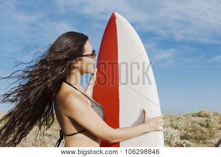 Half length portrait of a young brunette hair model in bikini preparing for surfing in the ocean in