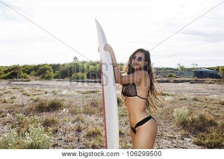 Portrait of a young charming women with perfect figure posing outdoors with her surfboard in sunny d