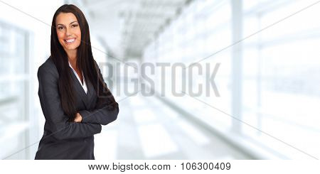 Young smiling business woman over office background.