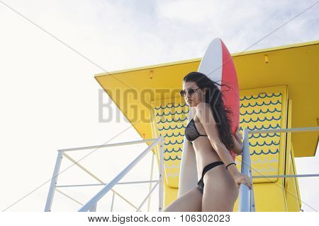 Portrait of a young charming Latin women in sexy bikini standing on lifeguard house with her surfboa