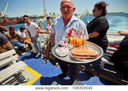 Waiter Of The Ferry With Serves Drinks And Snacks On Board